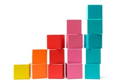Putting the final building block onto the top of a rising pile signifying success and achievement.
